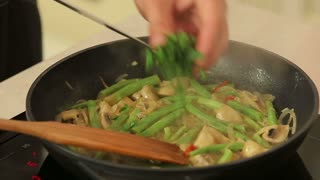 Chef is frying vegetables on a pan