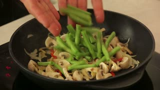 Chef is frying vegetables on pan