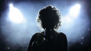Female singer backlit on smoky stage
