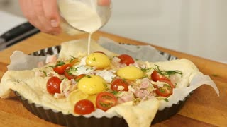 Raw homemade pie with eggs, vegetables and ham ready for baking