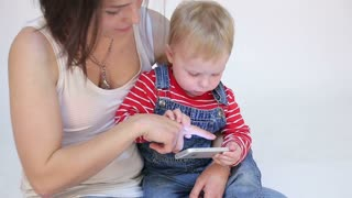 Young mother and kid son playing with mobile phone