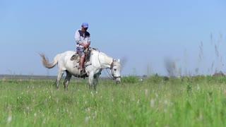 Herdsman on a horse looking at camera