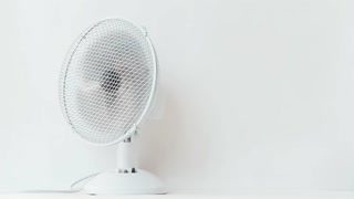 Rotating electric fan on white background