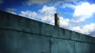 Barbed wire and concrete wall on a sunny day. This clip is loop ready.