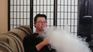 Man sitting on sofa at home using vaporizer smoking alternative