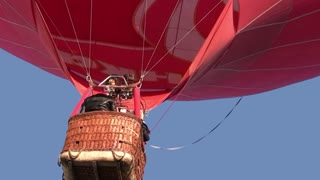 Red hot air balloon rises slowly in the air. In a gondola unrecognizable person operates a gas burner flame