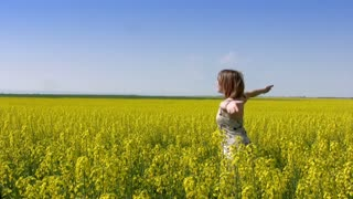 Teen girl closed her eyes and spins with his arms raised in a field of canola. Clear sunny skies. A vast field of yellow flowers. Dizzy and girl fell into the soft grass