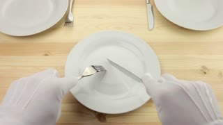 White plate. Hands in white gloves with a fork and a knife cut a piece of invisible food