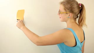 Young girl fun painting the walls with a paintbrush