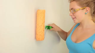 Young girl gaily painting the walls in orange with a paint roller