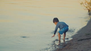 A boy playing near the water