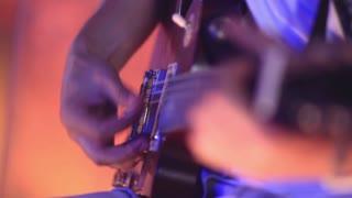 A man plays the guitar.