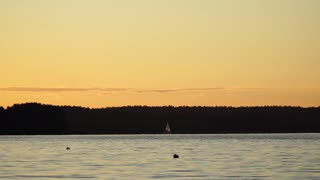 A small sailing boat on the water at sunset