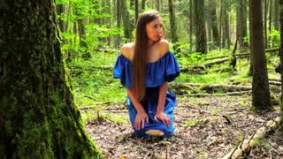 A woman in a blue dress found a big mushroom among wild forest. mystical mood.
