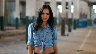 Beautiful brunette moves the camera, in a denim shirt