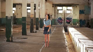 Beautiful girl walking in an abandoned building