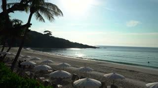 Beautiful sandy beach. Bay Ocean hidden cliffs. Sun loungers and umbrellas to protect tourists from the sun.