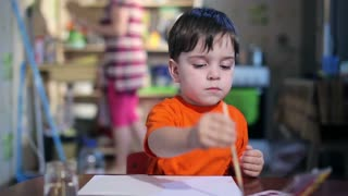 boy at the table draws with a brush