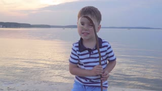 Caucasian boy in a striped vest on the waterfront. Joyful in the background yachts, sunset.