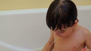 Emotional little boy taking a bath alone.