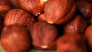 Filbert or wood nut shelled nuts closeup slowly rotate
