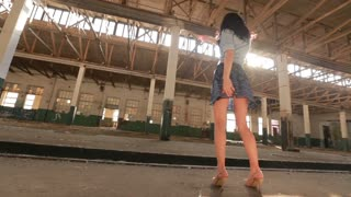 Girl dancing in an abandoned factory in the sun, and the dust raised