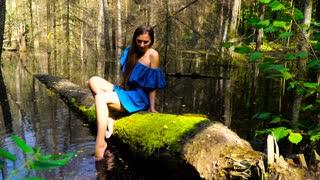 Girl in a blue dress sitting on a fallen tree in the wilderness