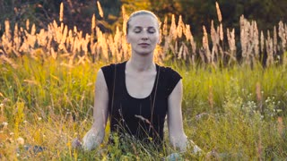 Girl meditates in nature, in the evening in the tall grass, sunlight in the 4 to the resolution