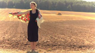 Girl on a background of field in a strong wind.