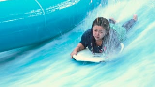 Girl on the board in the water park. Strong current does not allow the girl to her feet. The girl lies on a surfboard