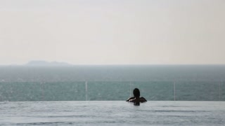 Girls in luxury hotel looking at the ocean. The blue tones