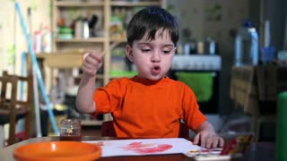 Joyful child at the table with a brush