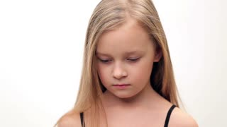 Little girl with blond hair shows sadness, sorrow.