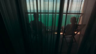 Man and woman sitting on a balcony overlooking the ocean, talking to each other