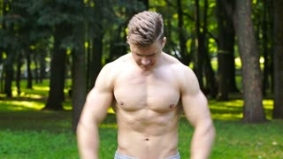 man with a beautiful body, do exercises in the park