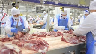People prepare fresh meat for delivery to stores
