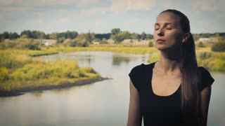 Portrait of a young woman who meditates on a background of nature with eyes closed
