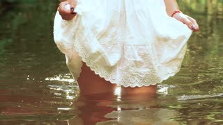 She enters the river, picking up a little dress exposing beautiful legs