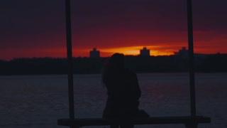 Silhouette of a girl sitting on a bench and admire the sunset
