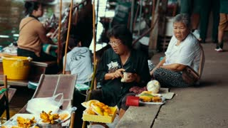 Thailand Bangkok November 20 Tourists eat on the floating market. Woman on the boat driving up food.