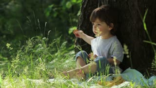 The child eats in nature
