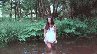 The girl walks on a shallow river. in a bright dress