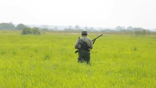 The hunter in the field with setter shooting at a flying bird, snipe