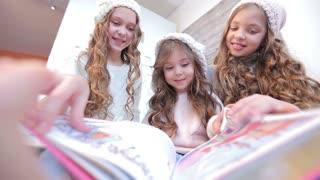 Three girls looking book