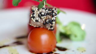 Tuna with cherry tomatoes on a skewer with sesame seeds. Cold appetizer