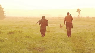 Two hunters with dogs are on the hunt for a field