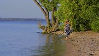 A beautiful girl strolls along the edge of the water. A happy and smiling woman with long hair walks along the sand of a large pond. Camera movement behind the subject