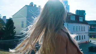A girl with beautiful long hair goes straight to the camera. strolls down the street