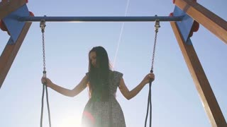 Girl Asian appearance riding on a swing