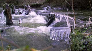 Icicles on a winter forest river with a rapid current